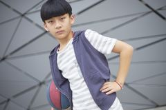 Portrait of cool Asian kid holding basketball outdoors Stock Photos