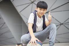 Portrait of cool Asian kid holding basketball outdoors Stock Image