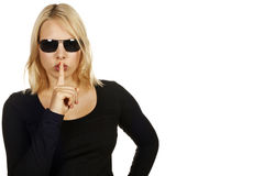 Portrait of a cool attractive blonde girl hushing. Royalty Free Stock Photography