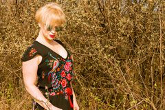 Portrait of cool fashionable woman wearing dress and shades. In the sun outside on countryside background with copypsace advertising area Royalty Free Stock Photos
