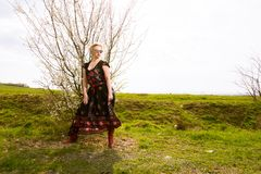 Portrait of cool fashionable woman wearing dress and shades. In the sun outside on countryside background with copypsace advertising area Royalty Free Stock Photography