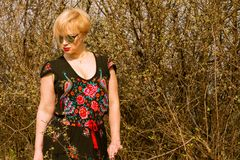 Portrait of cool fashionable woman wearing dress and shades. In the sun outside on countryside background with copypsace advertising area Stock Images