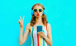 Portrait cool girl blowing red lips sending sweet air kiss holding phone listening to music in wireless headphones on colorful stock photos