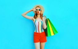 Portrait cool girl blowing red lips sends air kiss posing with shopping bags in colorful t-shirt, summer straw hat on blue royalty free stock images