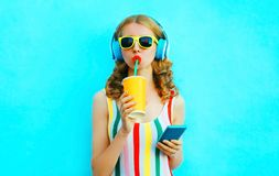 Portrait cool girl drinking fruit juice holding phone listening to music in wireless headphones on colorful blue royalty free stock images