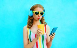 Portrait cool girl drinking fruit juice holding phone listening to music in wireless headphones on colorful blue royalty free stock photos