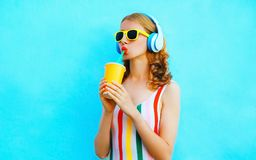 Portrait cool girl drinking fruit juice listening to music in wireless headphones on colorful blue. Background stock photography