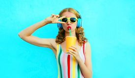 Portrait cool girl drinking fruit juice listening to music in wireless headphones on colorful blue royalty free stock photos