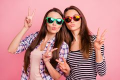 Portrait of cool gorgeous ladies students coquettish attract boys wearing eye glasses making v-signs having weekends. Rest relax dressed in colorful shirts stock photos