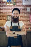 Portrait of a cool hairstylist looking at camera with confidence. Portrait of a cool bearded hairstylist wearing wristwatch, apron and cap while looking at Stock Photos