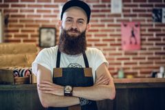 Portrait of a cool hairstylist looking at camera with confidence. Portrait of a cool bearded hairstylist wearing wristwatch, apron and cap while looking at Stock Image