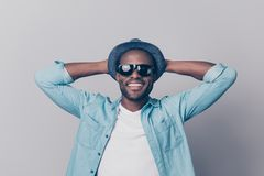Portrait of cool handsome careless afro guy dressed in denim clo. Thes black dark glasses holding hands behind head enjoying his free time isolated on gray Stock Photo