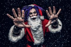 Cool punk santa. Portrait of a cool punk Santa Claus with bright dreadlocks over black background stock photos