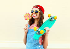 Portrait cool smiling girl with lollipop and skateboard over white Royalty Free Stock Image