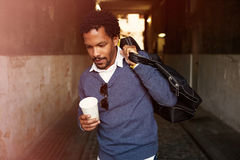 Portrait of a cool travel black guy walking with coffee. Stock Photography