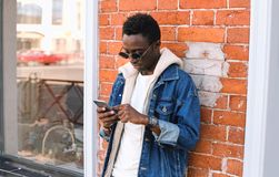 portrait cool urban african man with phone on city street over brick wall stock images
