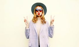 Portrait cool woman blowing red lips sending air kiss in round hat. On wall background stock photography