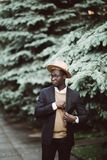 Portrait of a cool young afro american man in suit and hat walking in the street stock photos