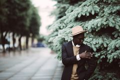 Portrait of a cool young afro american man in suit and hat walking in the street royalty free stock image