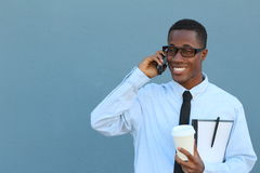 Portrait of a cool young African man in suit and tie walking and talking on mobile phone.  Royalty Free Stock Photo