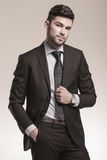 Portrait of a cool young business man posing. In studio on gray background Royalty Free Stock Image