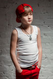 Portrait of cool young hip hop boy in red hat and red pants. And white shirt in loft Stock Photo
