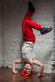 Portrait of cool young hip hop boy standing on his head. Portrait of cool young hip hop boy in red hat and red pants and white shirt standing on his head in the Royalty Free Stock Photos
