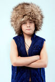 Portrait of cool young stylish boy in fur hat Royalty Free Stock Images