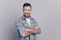 Portrait with copy space of young attractive, stunning, smiling. Man having his hands crossed, looking at camera, standing over grey background Royalty Free Stock Images