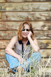 Portrait country woman with red hair leaning against timber shed Royalty Free Stock Image