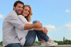 Portrait of a couple. Sat together in field Stock Photography