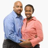 Portrait of couple. Portrait of African American couple with arms around eachother against white background Stock Photography