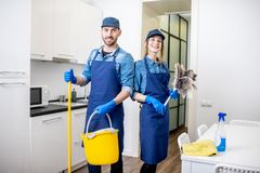 Man and woman as a professional cleaners indoors. Portrait of a couple as a professional cleaners in uniform standing together with cleaning tools indoors stock photos