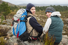 Portrait of a couple with backpack relaxing while on a hike Stock Photos