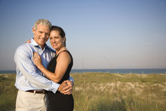 Portrait of Couple on Beach. Attractive causcasian couple embrace and smile at the camera. Horizontal shot Stock Images