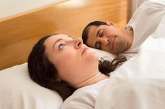 I can not sleep tonight. Portrait of couple in bed while women with sleeplessness  thinking on her preoccupations while the husband sleep placidly Royalty Free Stock Images