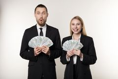 Portrait of couple in black suits shocked holding money banknotes in hands royalty free stock photos