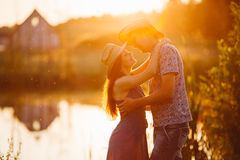 Portrait of couple of brunette woman and man standing on pier of lake at sunset, embracing and smiling. Girlfriend and boyfriend s Royalty Free Stock Photo