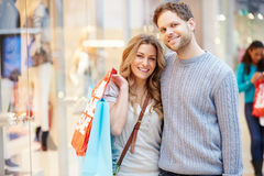 Portrait Of Couple Carrying Bags In Shopping Mall. With Arms Around Each Other Smiling To Camera Stock Image