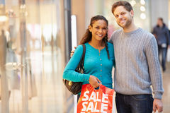 Portrait Of Couple Carrying Bags In Shopping Mall Royalty Free Stock Photography
