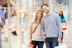 Portrait Of Couple Carrying Bags In Shopping Mall. Looking At Camera Smiling Stock Photo