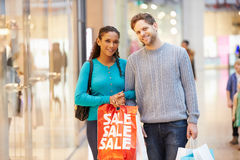 Portrait Of Couple Carrying Bags In Shopping Mall Stock Photography