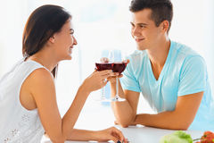 Portrait of couple clinking their glasses of red wine in the kit Stock Photos