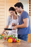 Portrait of a couple cooking with a pan Stock Image