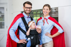 Portrait of couple costume feeding milk to daughter at home Stock Photo
