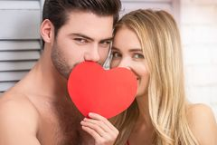 Couple covering faces with red paper heart. Portrait of couple covering faces with red paper heart at home stock photo