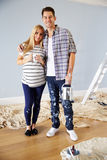 Portrait Of Couple Decorating Nursery For New Baby Stock Image