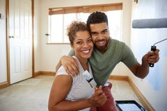 Portrait Of Couple Decorating Room In New Home Painting Wall Together royalty free stock images