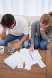 Portrait of a couple doing their accounting. In their living room Stock Images