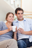 Portrait of a couple drinking coffee while watching TV Stock Images